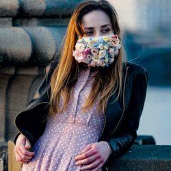 امرأة ترتدي قناعاً مزيناً بالورود على جسر تشارلز في براغ عاصمة جمهورية التشيك (أ.ف.ب)