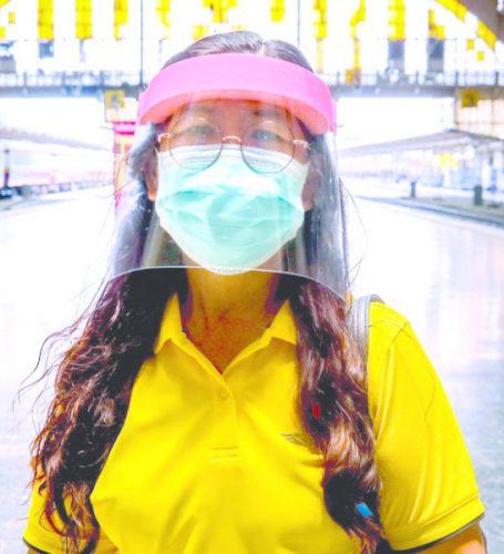 تايلاندية ترتدي كمامة واقية بالإضافة لدرع للوجه في محطة للسكك الحديدية في بانكوك