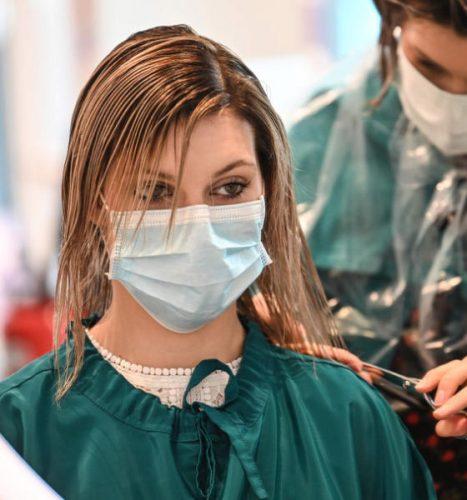 فرنسية تصفف شعرها خلال تجربة تشغيل صالونات التجميل بفرنسا