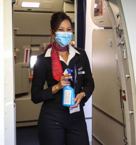 مضيفة ترتدي كمامة وتحمل معقماً عند مدخل طائرة في مطار بروكسل