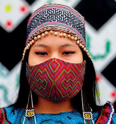 شابة بيروفية ترتدي قناعاً بنقوشات تقليدية أثناء الاحتفال بفعاليات اليوم العالمي للسكان الأصليين في مدينة ليما عاصمة بيرو (أ.ف.ب)