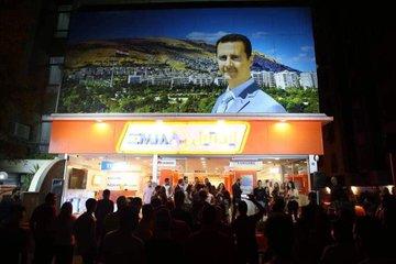 """سوريا في صورتين: أقفاصٌ لخبزِ الفقراء وطابورٌ لشراء """"الآيفون"""""""